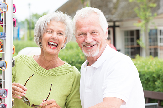 Couple of retirees laughing while shopping for sunglasses